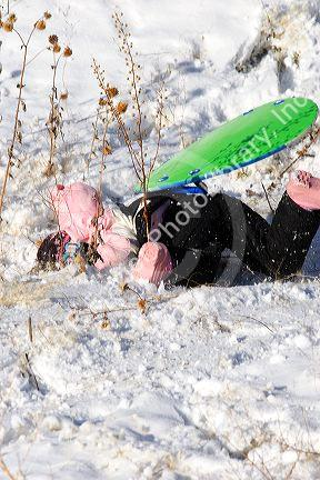 A young girl crashes while sledding on a snow covered hill in Idaho. MR