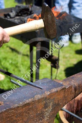 Blacksmith using a hammer to work with heated iron during a civil war reenactment near Boise, Idaho.