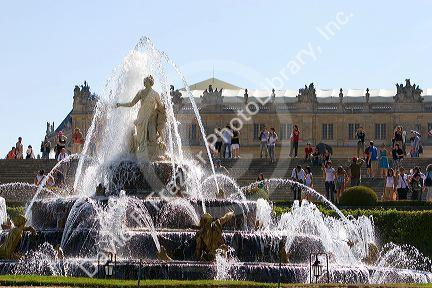 Tourists enjoy a water fountain in the formal gardens at The Palace of Versailles at Versailles in the department of Yvelines, France.