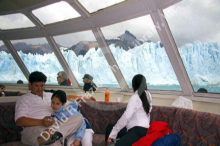 Family on a tour boat at the Perito Moreno Glacier located in the Los Glaciares National Park in the south west of Santa Cruz province, Patagonia, Argentina.
