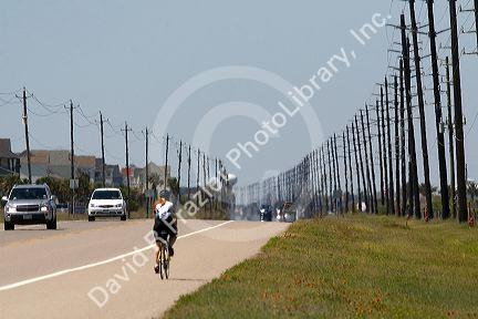 Utility poles line a highway on Galveston Island in Galveston, Texas.