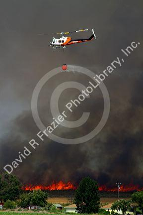 Helicopter with water bucket performing aerial firefighting on a wildfire in Eagle, Idaho, USA.