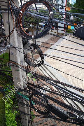 Utility pole with assorted cables and wires in Bangkok, Thailand.