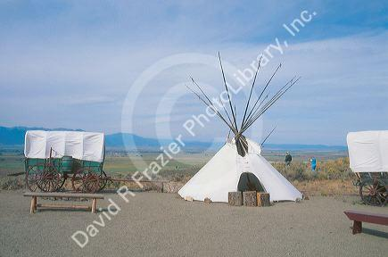 A covered wagon and teepee stand outside of the Oregon Trail Museum in Baker, Oregon.
