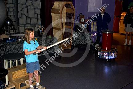 A girl holding a light tube demonstrating a Tesla coil with lightning at the Discovery Center in Little Rock, Arkansas.