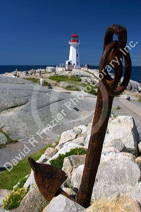 Large rusty anchor in front of a lighthouse at Peggy's Cove, Nova Scotia, Canada.
