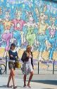 Mural with girls walking in front of it in Venice Beach, California.