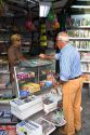 French man purchasing a newspaper from a Presse news kiosk in Sanary-sur-Mer, France.